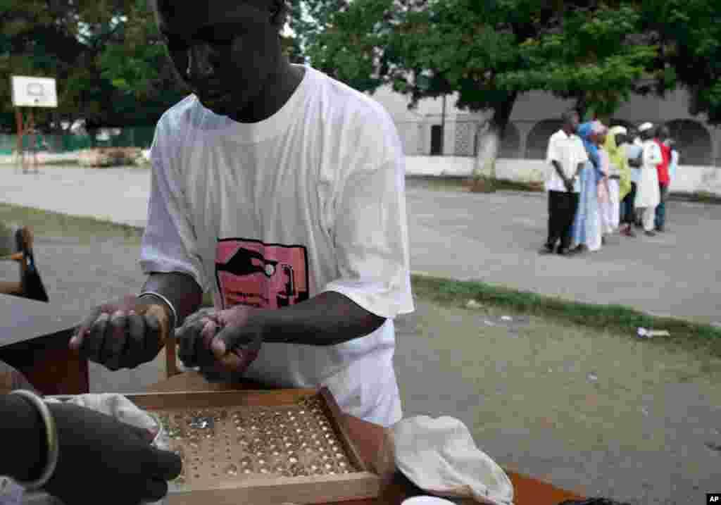 Des employés comptent les billes lors de l'élection présidentielle à Banjul, en Gambie, le 22 septembre 2016.