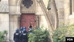 Image d'archives uniquement à titre d'illustration : la police anti-émeute enfonçant une porte d'une église à Saint-Denis, près de Paris, France, le 18 novembre 2015. (Photo: D. Schearf / VOA)