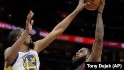 Košarkaš Golden Stejt Voriorsa Kevin Durent blokira šut Lebrona Džejmsa (Klivlend) u drugom poluvremenu treće utakmice finala NBA plej-ofa u Klivlendu (Foto: AP/Tony Dejak)