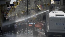 Riot police clash with demonstrators after they used tear gas and pressurized water in a dawn raid Friday, Turkey, May 31, 2013.