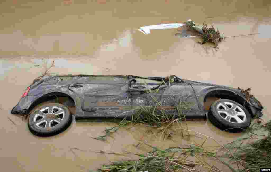 A car is seen submerged following floods in Livorno, Italy.