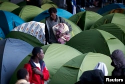 With police present, social workers evacuate migrants from a tent camp under the Charles de Gaulle Bridge along the Seine in southeast Paris, Sept. 17, 2015.