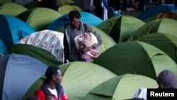 Socijalni radnici evakuišu migrante iz kampa koji su podigli ispod mosta Šarl Degol na Seni, u Parizu, 17. septembra 2015.
