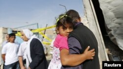 Seorang pria menggendong putrinya melintasi rumah warga sipil yang hancur akibat serangan mortir di wilayah pemukiman Akcakale, Turki (4/10). Lima orang dikabarkan tewas dalam insiden tersebut.