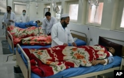 FILE - Doctors assist wounded in a hospital after they were injured in a suicide attack, inside a resident house, in Jalalabad, capital of Nangarhar province, Afghanistan, Jan. 17, 2016.