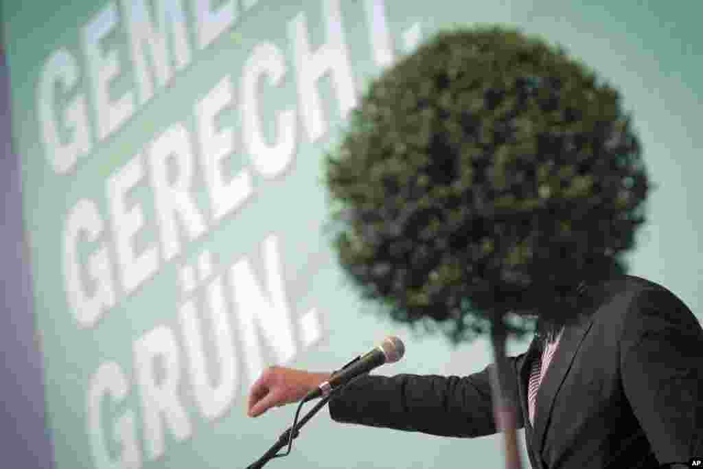 German Greens' top candidate for the upcoming general elections Juergen Trittin is hidden behind a shrub as he speaks during a party convention in Bingen, western Germany.