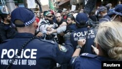 Protesters clash with police on a street in Sydney's central business district in Australia, September 15, 2012.