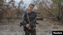 Seorang perempuan yang ikut bertempur dengan para pemberontak pro-Rusia dengan senjatanya di Nizhnaya Krinka, Ukraina timur (23/9). (Reuters/Marko Djurika)