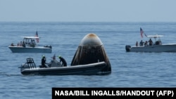 This handout photo released courtesy of NASA shows support teams and curious recreational boaters approaching the SpaceX Crew Dragon Endeavour spacecraft shortly after it landed. (NASA)