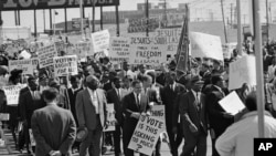 FILE - Part of the group of marchers, estimated at over 2,000 parade through downtown Dallas, Texas on March 14, 1965, in support of the African American voter registration in Selma, Alabama.
