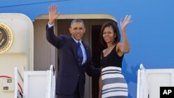 President Barack Obama and first lady Michelle Obama wave prior to boarding Air Force One before departing for a week-long trip to Senegal, South Africa, and Tanzania, June 26, 2013.