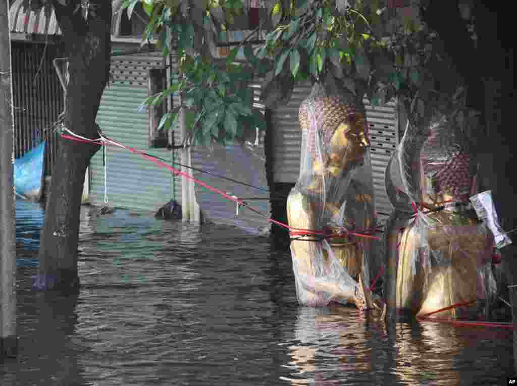 Buddha images are wrapped in plastic and tethered to trees so they don't float away in the waist-deep water in Phet Kasem, Bangkok, November 9, 2011. (VOA - G. Paluch)