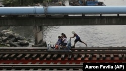 In this Wednesday, Aug. 12, 2015 photo, a man pushes a metal-wheeled cart with benches fashioned from scrap wood as he ferries passengers for 10 pesos each along the railway in Manila. (AP Photo/Aaron Favila)