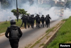 FILE - Ivory Coast riot policemen disperse opposition supporters with tear gas during a march to protest against Ivory Coast's President Alassane Ouattara's new constitution in Abidjan, Ivory Coast, Oct. 20, 2016.
