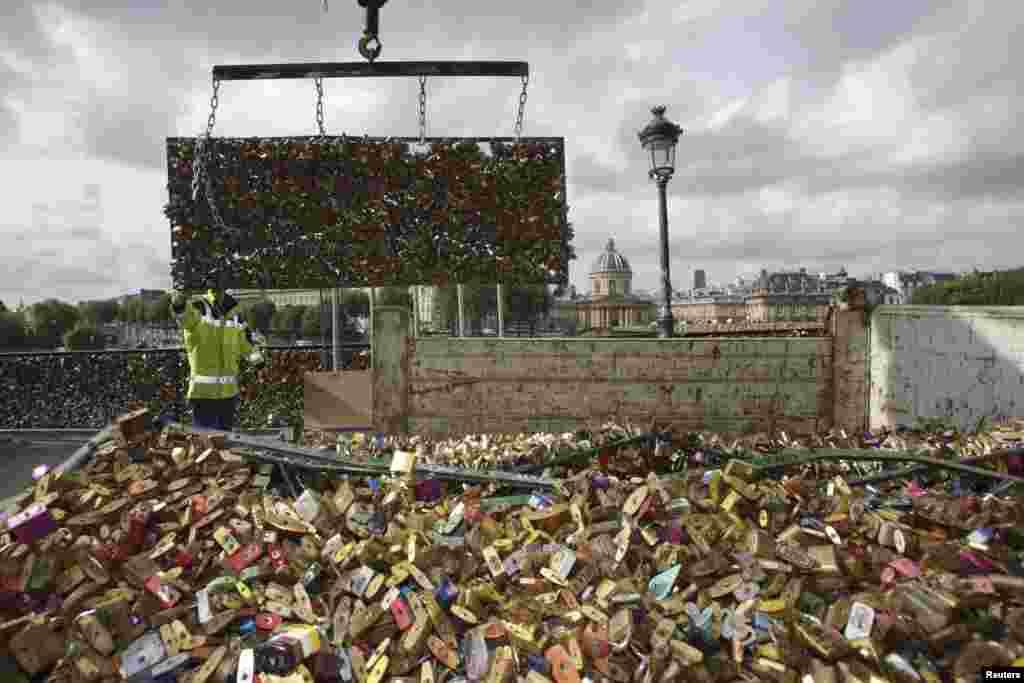 """Pegawai pemerintah kota menurunkan pagar besi yang penuh dengan """"gembok cinta"""" ke sebuah truk setelah dipindahkan dari Pont des Arts di Paris, Perancis. Jembatan tersebut ditutup dari tanggal 1 Juni sampai 8 Juni untuk memindahkan gembok-gembok tersebut."""