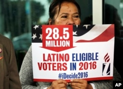 FILE - Georgina Arcienegas holds a sign in support of Latino voters during a protest outside the office of Florida Rep. Carlos Trujillo, Jan. 12, 2016, in Doral, Florida.
