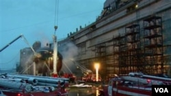 Para petugas pemadam kebakaran Rusia menyemprotkan air ke arah kapal selam Yekaterinburg di kawasan Murmansk, Rusia (30/12). 9 petugas kebakaran dikabarkan cedera akibat menghirup asap kebakaran.