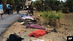 Bodies seen by roadside near the mangled wreckage of a bus which hit a landmine planted by maoist rebels in Dantewada district of Chhattisgarh, India, 17 May 2010