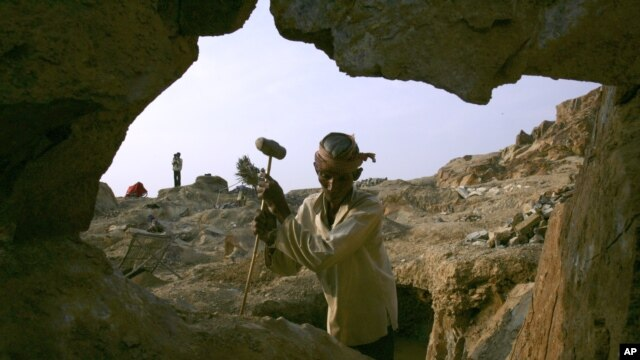 Cambodian It On, 60, holds a hammer for breaking stone used in construction at Phnom Baseth hill, file photo.