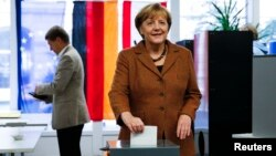 German Chancellor Angela Merkel poses as she casts her ballot during general elections at a polling station in Berlin, September 22, 2013. The person in the background is Merkel's husband, Joachim Sauer.