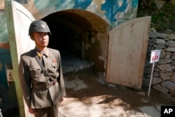 FILE - In this May 24, 2018 photo, a guard stands at the entrance of the north tunnel at North Korea's nuclear test site, which was blown up soon after this photo was made, in a display of dismantling the test site, at Punggye-ri, North Hamgyong Province, North Korea.