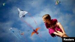 Madeleine Klonoski, 2, sits on her father's leg at a kite festival in Redondo Beach, California, March 8, 2015.