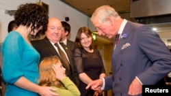 Britain's Prince Charles (R) speaks to Clare Curran and her daughter Jessie, 6, during a visit to mark National Police Memorial Day at St David's Hall in Cardiff, Wales, Sep. 29, 2013.