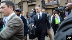 Oscar Pistorius, center, leaves after the court adjourned for the day in Pretoria, South Africa, on May 6, 2014.