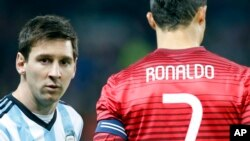 Lionel Messi de l'Argentine, à gauche, se tient à côté de Cristiano Ronaldo du Portugal avant un match amical international entre la sélection argentine et la portugaise à Old Trafford Stadium, Manchester, Angleterre, 18 novembre 2014. (AP Photo / Jon Super)