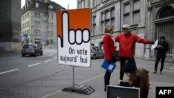 30일 스위스 프리부르주 거리에 '우리는 오늘 투표한다' 라는 글귀가 프랑스어로 쓰여진 푯말이 서 있다.