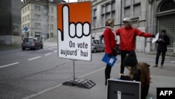 "People stand next to a board reading in French ""We vote today"" in the old town section of Fribourg, Switzerland, Nov. 30, 2014."