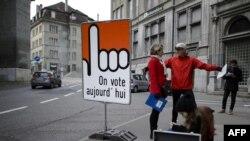 "Orang-orang berdiri di papan bertuliskan ""Kami memilih hari ini"" dalam bahasa Perancis di kota tua Fribourg, Swiss, 30 November 2014."