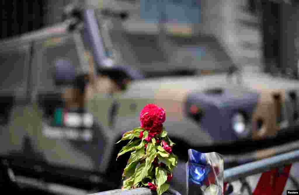 Flowers placed to pay tribute to the victims of the Bastille Day truck attack in Nice are seen in front of a military armoured vehicle at the French embassy in Rome, Italy, July 15, 2016.