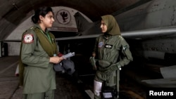 Ayesha Farooq, a fighter pilot, talks with avionics engineer Anam Hassan at Mushaf base in Sargodha, north Pakistan June 7, 2013.