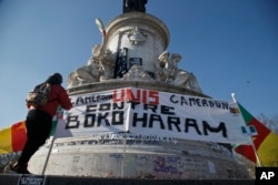 "A Cameroonian man living in exile in France adjusts a banner that reads,""Cameroon united against Boko Haram,"" at the Republique plaza in Paris, Feb. 7, 2015."