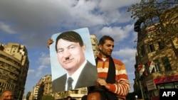 Kahire'deki Tahrir Meydanı'nda Devlet Başkanı Hüsnü Mübarek'in resmini Adolf Hitler gibi gösteren bir poster taşıyan Mısırlı gösterici
