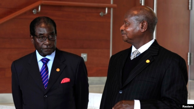 Zimbabwe President Robert Mugabe (L) stands next to his Ugandan counterpart Yoweri Museveni while marking the 50th anniversary of the establishment of the Organization of African Union (OAU) in Addis Ababa, May 25, 2013.