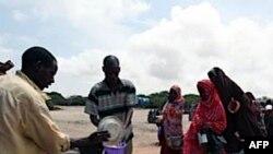 Голодні сомаліці стоять в черзі, щоб отримати їжу