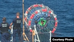 Reza Baluchi is seen in his bubble after the Coast Guard plucked him out of the water Sunday. (USCG via Twitter)