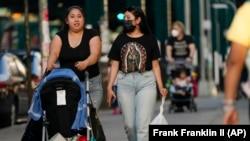 Two women -- one with a mask, one without -- walk along Roosevelt Avenue in the Queens borough of New York, May 19, 2021. (AP Photo/Frank Franklin II)
