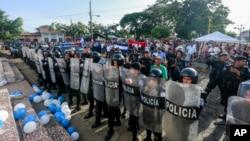 Policías forman un cordón afuera de la iglesia donde se celebra una misa por la libertad de los presos políticos, en Masaya, Nicaragua. Foto de archivo AP.