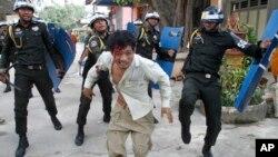 Seorang demonstran yang terluka melarikan diri dari kejaran polisi anti huru-hara di komplek pagoda Budha di Phnom Penh, Kamboja (12/11).