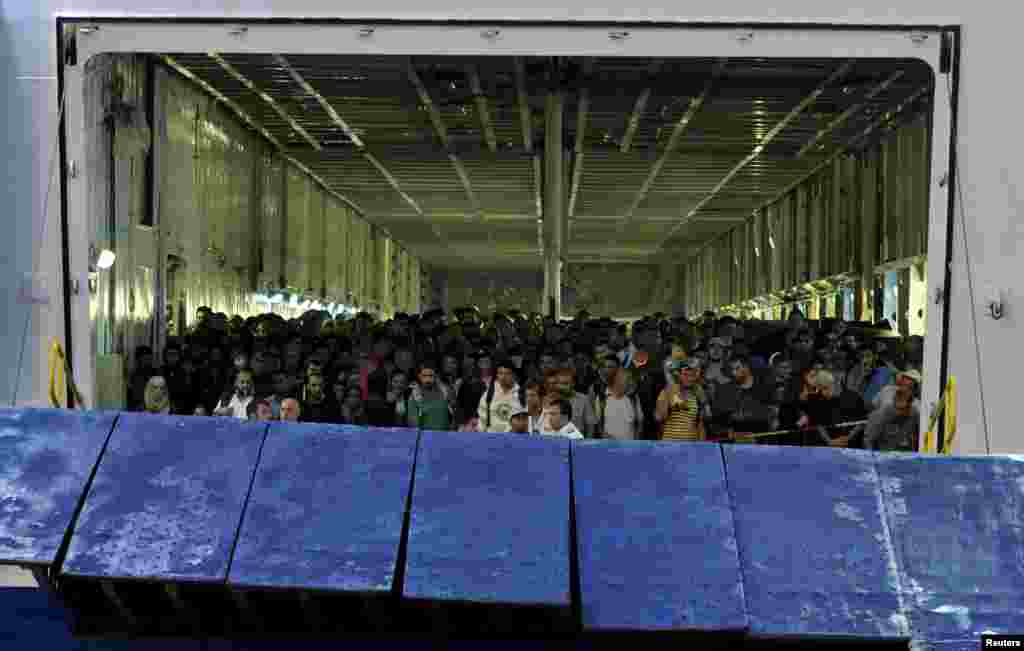 Syrian refugees wait to disembark a passenger ship at the port of Piraeus, near Athens, Greece.