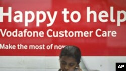 An employee talks on mobile phone inside a Vodafone store in Agartala, capital of India's northeastern state of Tripura, January 20, 2012.