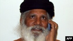 FILE - Hindu priest Bharatdas Darshandas talks on his mobile phone at a private news channel studio in Rajkot, India, March 2, 2009
