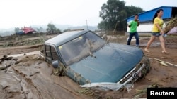 People walk past a car stranded in mud after heavy rainfalls hit Fushun, Liaoning province, August 17, 2013.