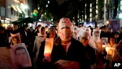 Para demonstran membawa lilin dan foot beberapa dari 43 mahasiswa yang hilang, di Mexico City, Jumat, 14 November 2014. (AP Photo/Eduardo Verdugo)