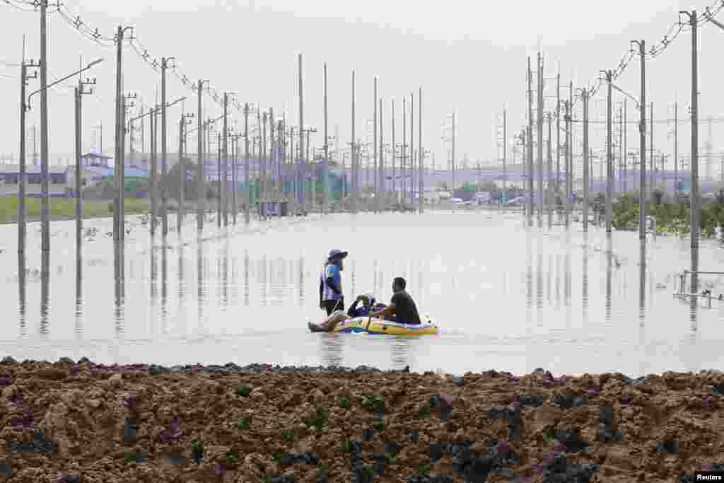 People are seen on a rubber boat along a flooded road at Amata Nakorn industrial Estate in Chonburi province, east of Bangkok, Thailand. Flooding at an industrial estate east of the capital has forced the closure of 2 foreign-owned factories producing electronic spare parts.