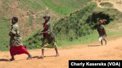 Des jeunes filles membres d'une milice marchent dans leur village, dans le Sud-Kivu, avril 2017. (VOA/Charly Kasereka)