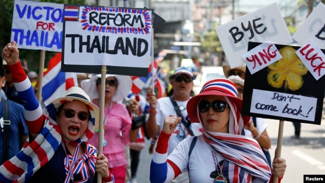 Anti-government protesters carry signs against ousted Prime Minister Yingluck Shinawatra as they march in central Bangkok, May 8, 2014.